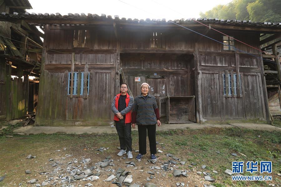 2016年12月15日,在贵州省榕江县崇义乡大塘村自家的老屋被拆除前,黄万鑫和母亲在老屋前留影。 新华社发(黄万鑫)
