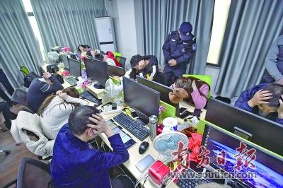 """2018年12月25日上午,""""客服人员""""刚开起镇日的做事就被警方逮个正着。南方日报记者 张梓看 摄"""