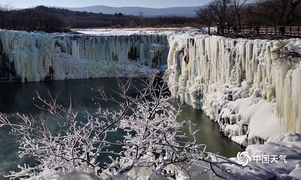 """吊水楼瀑布它位于暗龙江省宁安市西南部,镜泊湖之北端,是世界最大的玄武岩瀑布,水潭水深60米,叫""""暗龙潭"""",在冰天雪地的大东北,暗龙潭的水温却在8度旁边,是个不结冰的大水潭,上面是晶莹剔透的冰瀑布,雄浑大气、蔚为壮不悦目,是大自然创造的无声的波行。(文/肖鹏 图/李维华 拍摄于2018年12月28日)"""