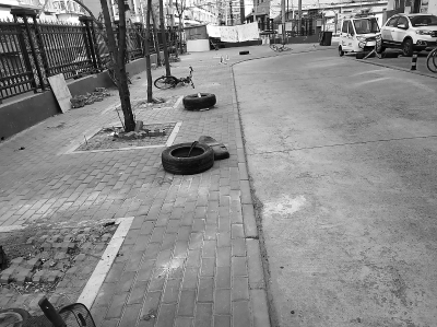 轮胎、自行车、地锁都成了抢占车位的工具.-轮胎占车位 搭棚堆杂物