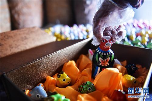 """3月5日,河南省浚县杨玘屯村,民间艺人正在将制作好的""""泥咕咕""""泥塑工艺品进行包装。"""