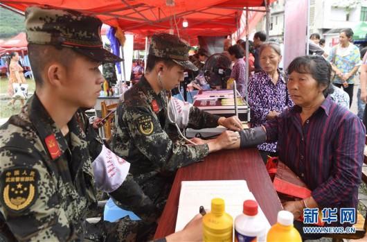 在四川长宁地震灾区安置点,武警宜宾支队卫生队党小组成员为群众提供医疗服务(6月20日摄)。新华社记者 刘坤 摄