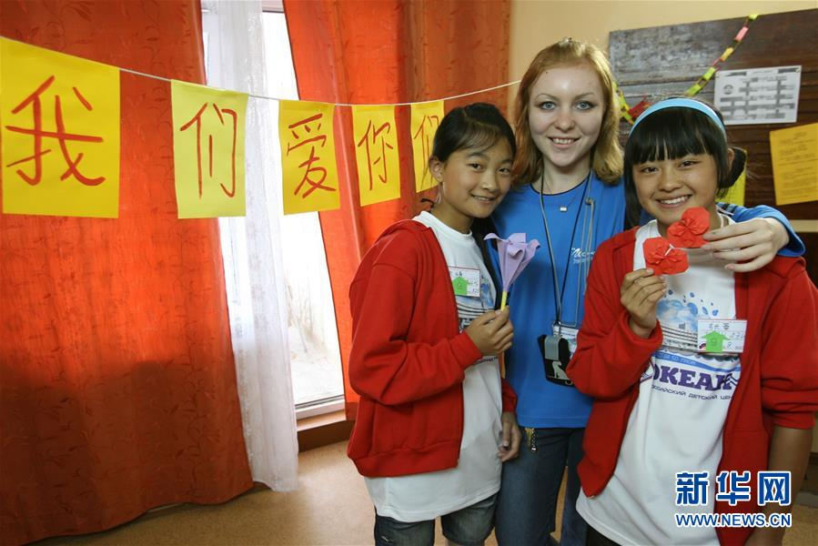 """2008年7月21日,在俄罗斯符拉迪沃斯托克的""""海洋""""全俄儿童中心,在此疗养的中国地震灾区小姑娘和她们的俄罗斯老师合影留念。新华社记者 郑悦"""