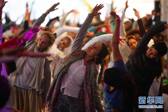 这是来自世界各地的瑜伽练习者在印度北阿肯德邦里希盖什举行的第16届国际瑜伽节开幕式上做瑜伽动作(2015年3月1日摄)。 新华社记者 郑焕松 摄