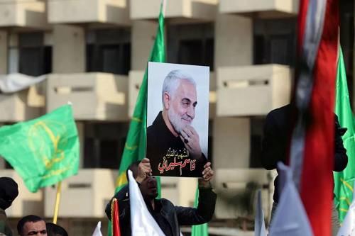 """当地时间1月4日,在伊拉克巴格达,哀悼者举着伊朗伊斯兰革命卫队下属""""圣城旅""""指挥官卡西姆·苏莱曼尼的画像参加送葬活动。(新华社)"""