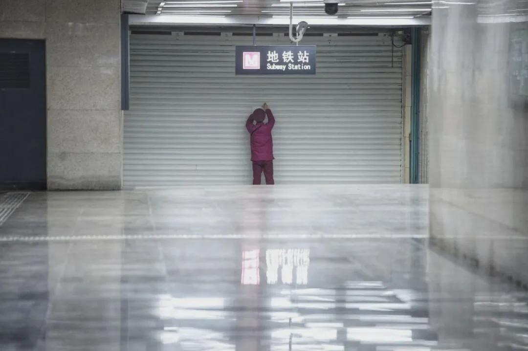 1月23日,武汉封城,市内公共交通停止运营。一位地铁工作人员正在粘贴告示。(来源 米拍 摄影 王效)