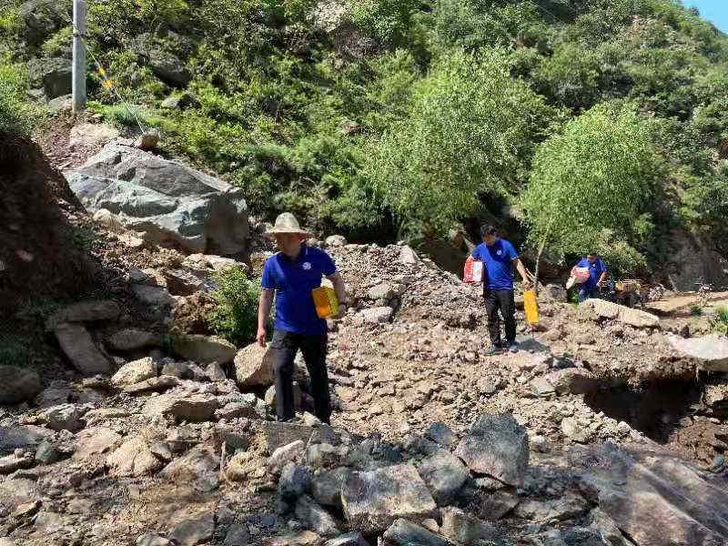 中国太保产险理赔工作人员在山区排查被冲车辆并安抚受灾百姓